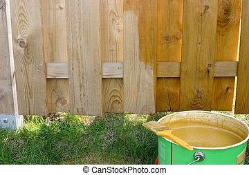 Painted fence - Half painted fence with paintbrush on the...