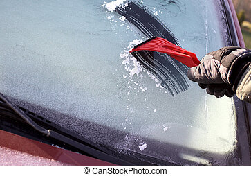 Scraping ice from the car winddow, with copy space on the...