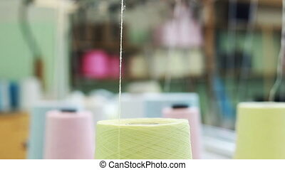 Twisting thread from bobbin on weaving loom - Twisting...