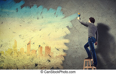 Young man and cityscape on the wall - Young man painting a...