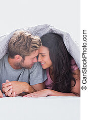 Couple under quilt hand in hand in their bed