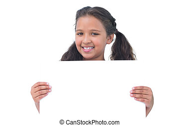 Smiling little girl holding and presenting sign at camera on...