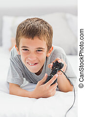 Concentrated little boy lying on bed playing video games
