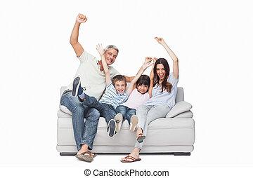 Family sitting on sofa raising their arms on white...
