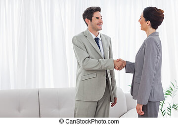 Smiling colleagues shaking hands during meeting at office
