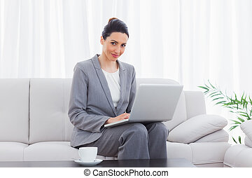 Smiling busineswoman sitting on sofa using laptop at office