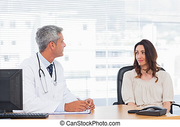 Doctor talking with his patient and writing on notebook in...