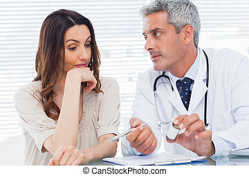 Serious doctor listening to his patient in medical office