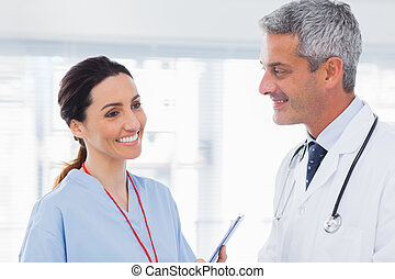 Nurse talking with doctor in medical office
