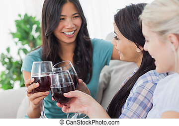 Chatting friends having red wine together at home on couch
