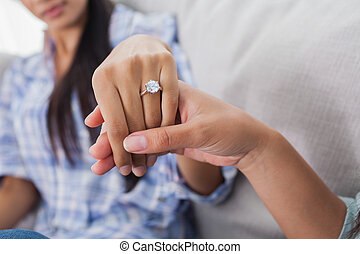 Engagement ring on woman's hand held by her friend