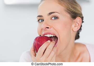 Attractive woman munching apple - Attractive woman in her...