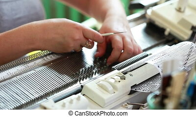 Woman straightens loops on knitting machine, close-up