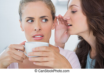 Woman telling secret to her friend while drinking coffee