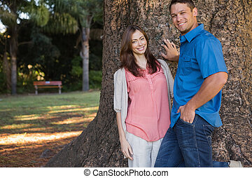 Couple leaning on a tree in a park smiling at camera