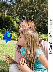 Mother with daughter blowing pinwheel in the park