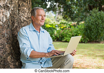 Mature man with a laptop looking into the sky