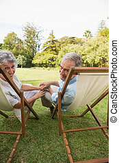 Smiling mature couple lying on sun loungers and looking at...