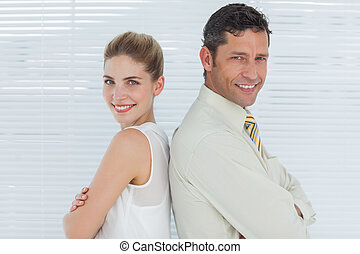 Smiling business team posing back to back