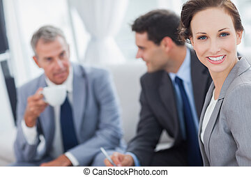 Cheerful businesswoman having a meeting with her colleagues...