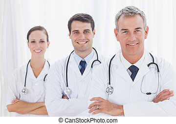 Smiling doctors posing together in bright office