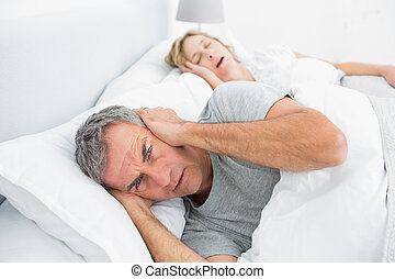 Annoyed man blocking his ears from noise of wife snoring at...