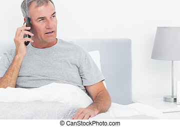 Grey haired man making a phone call