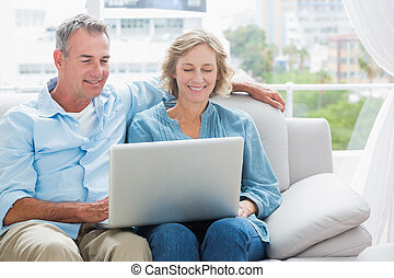 Cheerful couple relaxing on their couch using the laptop at...