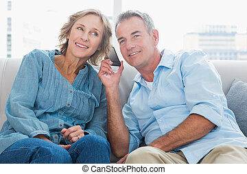 Cheerful couple listening to mobile phone together