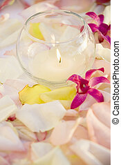 Lit candle with flowers. - Lit candle with purple orchids...