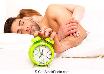 Couple is sleeping and the alarm clock starts to ring - time...