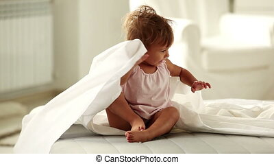 Child in bed - Cute little girl having fun lying in bed and...