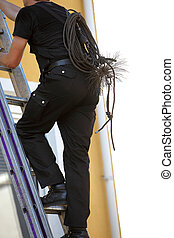 Chimney sweep climbing a stepladder with his equipment and...