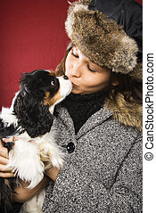 Woman kissing dog - Young adult Caucasian woman wearing fur...