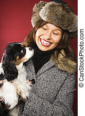 Woman holding dog. - Young adult Caucasian woman wearing fur...