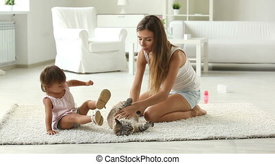 Family pet - Mom and daughter playing with their pet at home