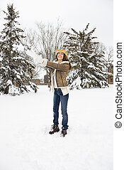 Woman throwing snow. - Caucasian young adult female standing...