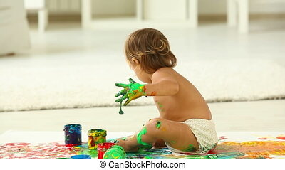 Colorful mess - Cute child playing with paints mixing the...