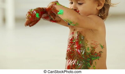 Dirty dancing - Child covered in paint moving, dancing and...