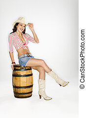 Cowgirl sitting on barrel - Young Caucasian woman dressed as...