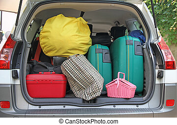 two green suitcases and many bags in the car - two green...