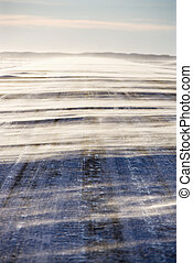 Ice covered road. - Ice covered road with snow being blown...
