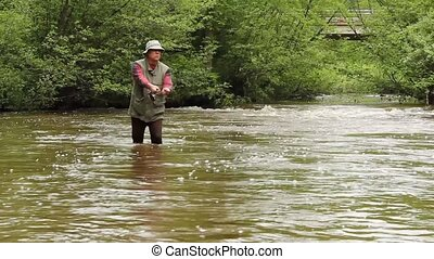 trout stream - trout fisherman in a stream walking toward...