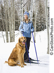 Woman and dog. - Mid adult smiling Caucasian female skier...