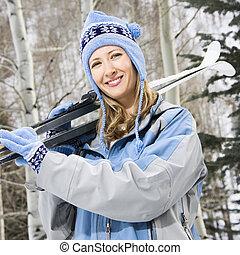 Female holding skis.