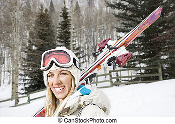 Smiling woman with skis - Attractive young blond woman in...
