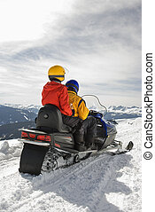 Couple on snowmobile - Man and woman riding on snowmobile in...