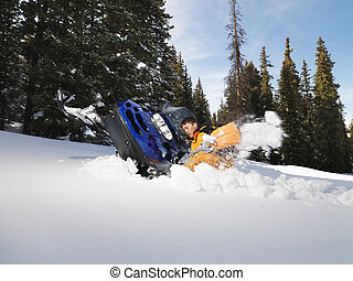 Man with stuck snowmobile - Young man digging out snowmobile...