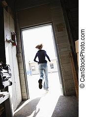 Woman running out door. - Woman running through open door...