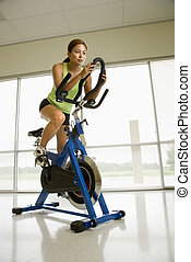 Woman exercising on bike. - Mid adult Asian woman pedaling...
